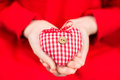Hands of a child holding a plaid red-white textile heart with button Royalty Free Stock Photo