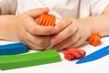 Hands of child molding from orange plasticine
