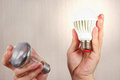 Hands compared incandescent bulb and glowing ecofriendly led lamp Royalty Free Stock Photo