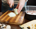 Hands cutting onion steps of cooking french style meat in roasting pan Stock Photography