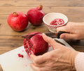 Hands cutting pomegranate four quarters Royalty Free Stock Photos