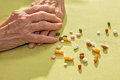 Hands of an elderly lady with medication clasped resting on a table alongside a variety scattered tablets capsule and pills Royalty Free Stock Photography