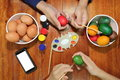 Hands of family members have a good time with coloring eggs prepare for easter day.