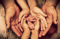 Hands of father, mother, daughter keep little feet baby. Friendly happy family Royalty Free Stock Photo