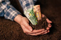 Hands with fertile soil and euro money banknotes Royalty Free Stock Photo