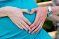 Hands folded mom and dad a heart on pregnant tummy Royalty Free Stock Photo