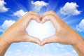 Hands in the form of heart with sunny sky Stock Image