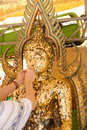 Hands gilding gold leaf onto the Buddha statue image.Which peopl Royalty Free Stock Photo