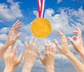 Hands with golden medal in front of blue sky Royalty Free Stock Images