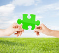 Hands with green puzzle over natural background Royalty Free Stock Photo