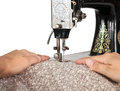 Hands guiding fabric through a vintage sewing machine two retro isolated on white Royalty Free Stock Photos