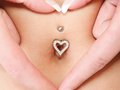 Hands heart symbol around navel piercing woman s forming a with mother awaiting for the baby Royalty Free Stock Photo