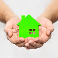 Hands hold green house on grey background Royalty Free Stock Images