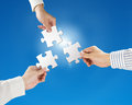 Hands hold puzzles with clear blue sky and sun light team work concept background Royalty Free Stock Photo