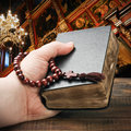 Hands holding the Bible and praying with a rosary Royalty Free Stock Photo