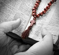 Hands holding the Bible and praying with a rosary Stock Photography