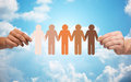 Hands holding chain of people pictogram over sky Royalty Free Stock Photo