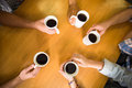 Hands holding coffee mugs on table Royalty Free Stock Photo