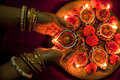 Hands holding diwali lamps female traditional earthen lit up in a line during festival in india Stock Images