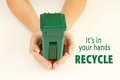 Hands holding a garbage container it s in your recycle Stock Image