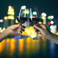 Hands holding glasses of red wine and clicking Royalty Free Stock Photo