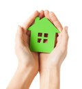 Hands holding green house closeup picture of woman Stock Photo