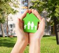 Hands holding green house with family real estate and home concept closeup picture of female paper Royalty Free Stock Photography