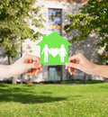 Hands holding green house with family real estate and home concept isolated picture of male and female paper Stock Photography