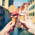 Hands holding ice cream in waffle cone.