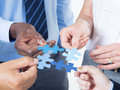 Hands Holding a Jigsaw with Business Concepts