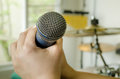 Hands holding a microphone in music room close up of karaoke Royalty Free Stock Photo