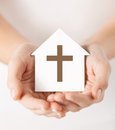 Hands holding paper house with cross symbol Royalty Free Stock Photo