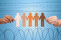 Hands holding people pictogram over barb wire