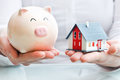 Hands holding a  piggy bank and a house model Royalty Free Stock Images