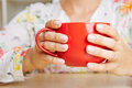 Hands holding red coffee cup female a big Royalty Free Stock Photography