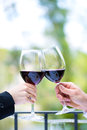 Hands holding red wine glasses to clink with outside on the terrace in a fine dining restaurant Royalty Free Stock Images