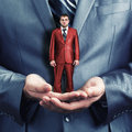 Hands holding small red businessman Stock Photo