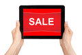 Hands holding a tablet with sale on a red screen female touch computer pad gadget the word Royalty Free Stock Images