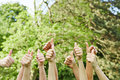 Hands holding thumbs up in nature many their green Royalty Free Stock Photo