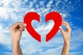 Hands holding two half of heart shape with blue sky Royalty Free Stock Photo