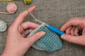Hands Knitting Wool with Balls of Yarn in Background Royalty Free Stock Photo
