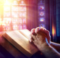 Hands of a man praying with bible Stock Photography