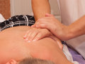 Hands of the masseur on body presses do massage motions Stock Image