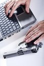 Hands mature adult man middle what seems to be hacking laptop computer hostile environment his left hand resting mm handgun his Stock Image