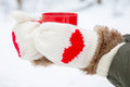 Hands in mittens with hearts holding cup warm red close up Royalty Free Stock Photography