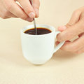Hands mixing with spoon of black coffee in the cup a Royalty Free Stock Images