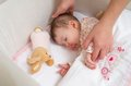 Hands of mother caressing her baby girl sleeping cute in a cot with pacifier and stuffed toy Royalty Free Stock Photo
