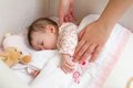 Hands of mother caressing her baby girl sleeping cute in a cot with pacifier and stuffed toy Stock Image