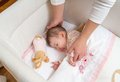 Hands of mother caressing her baby girl sleeping cute in a cot with pacifier and stuffed toy Stock Images