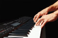 Hands of musician play the keys of the electronic piano on black background Royalty Free Stock Photo